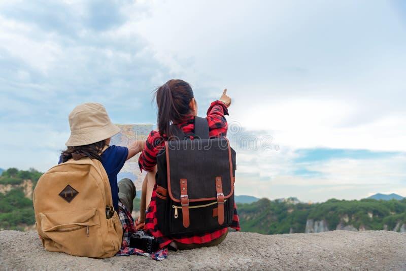 Mamá y niño que sostienen los mapas y las mochilas del viaje que sientan el revestimiento victorioso en el Gran Cañón para la nat foto de archivo