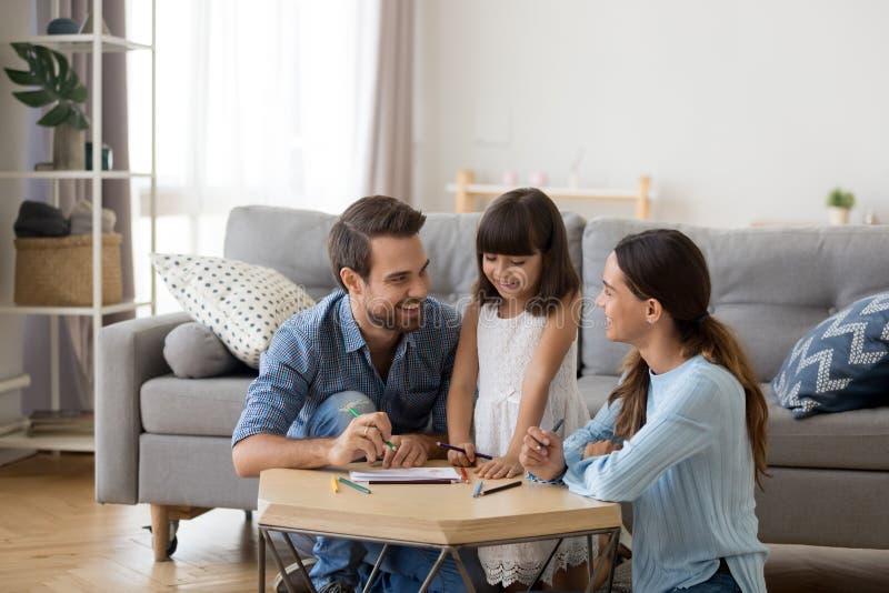 Mamá y papá que cuidan que enseñan a poca hija a dibujar foto de archivo