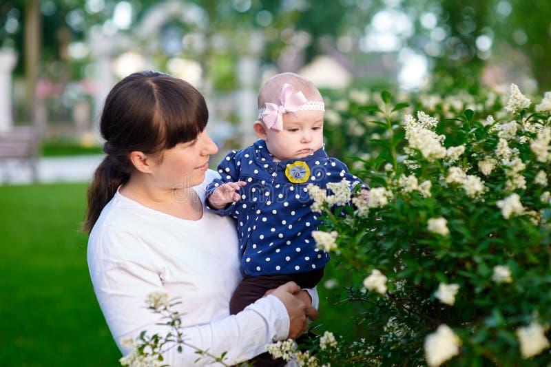 Mamá y pequeña hija que caminan en el parque imagen de archivo