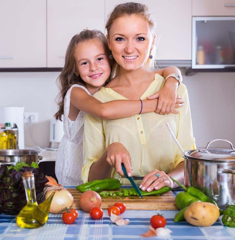 Mamá y pequeña hija que cocinan el plato vegeterian dentro imagen de archivo libre de regalías