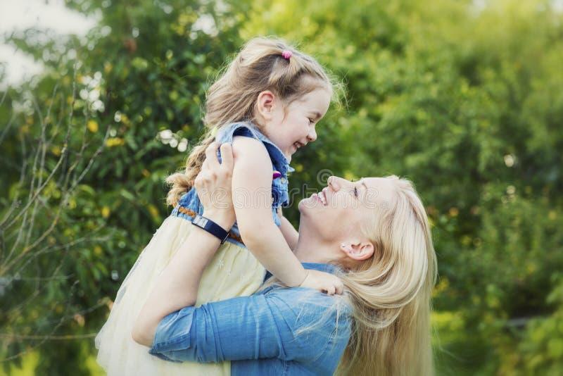 Mam? y risa y abrazo de la hija en el parque en verano Dulzura y amor fotografía de archivo libre de regalías