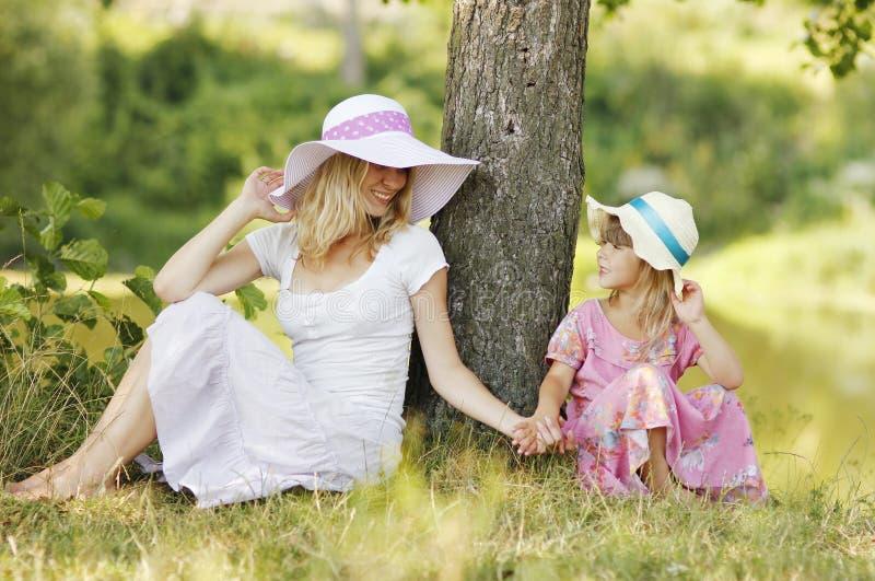 Mamá y su pequeña hija en los sombreros que se sientan cerca de un árbol imagen de archivo libre de regalías
