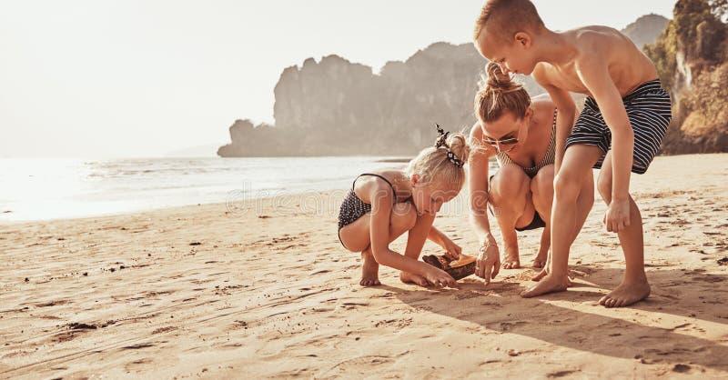 Mamá y sus dos niños que juegan en una playa arenosa fotografía de archivo libre de regalías