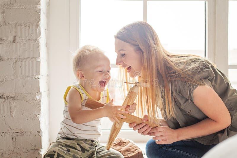 Mamá y sus juegos del hijo del niño con el juguete plano de madera foto de archivo