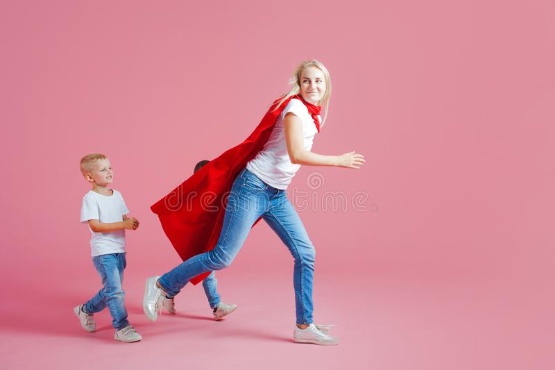 A mamã é um super-herói Família do divertimento, uma mulher loura nova em um cabo vermelho e seu filho Os filhos seguem a mamã imagens de stock