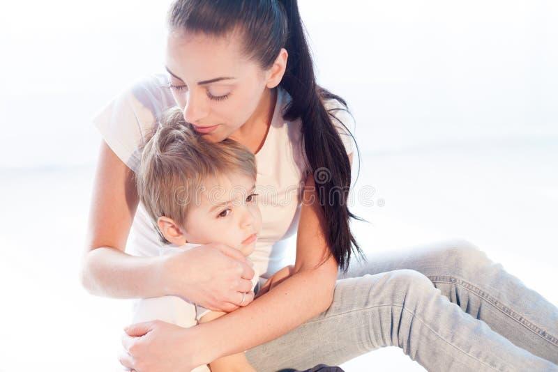 A mamã abraça seu amor da tristeza do filho fotografia de stock