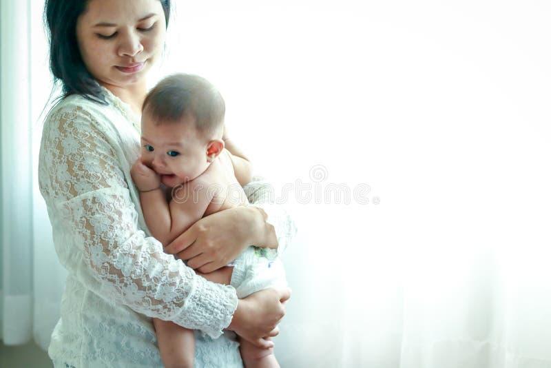 A mamã abraça um filho novo como um asiático fotos de stock