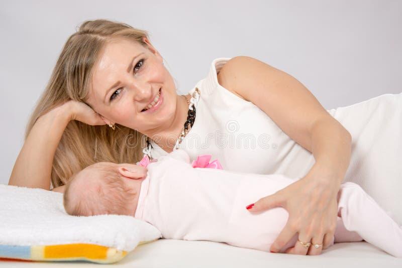 A mamã abraçou seu bebê que encontra-se ao lado dele imagem de stock