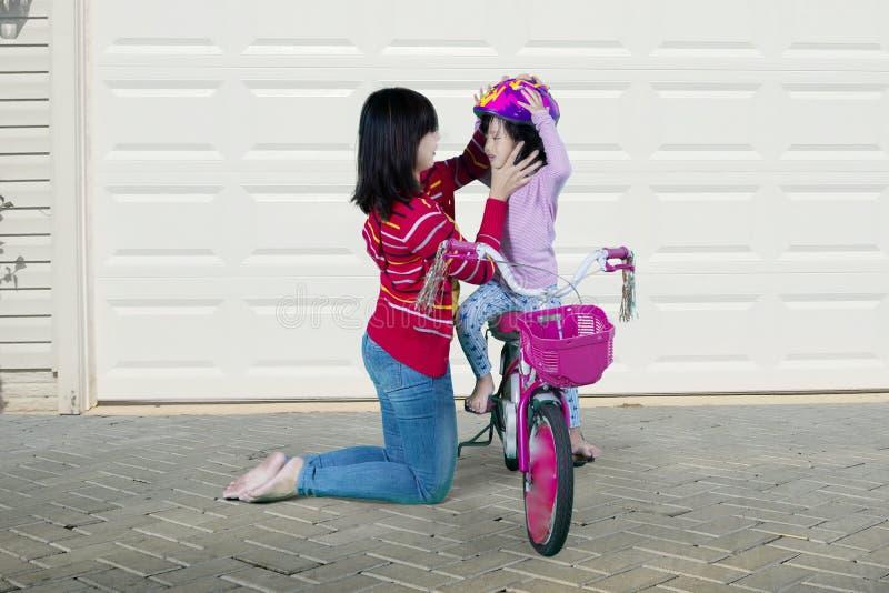 A mamã ajuda sua filha a prender um capacete fotografia de stock