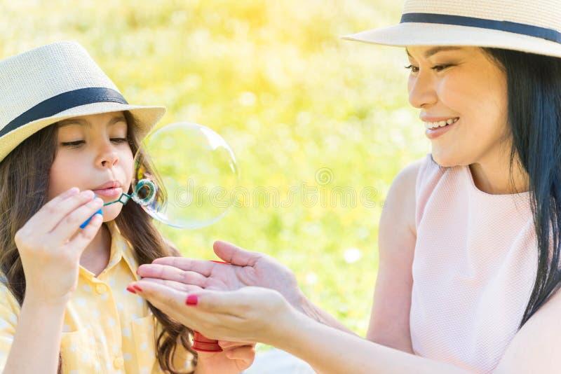 Mamã alegre e filha que jogam na pastagem fotografia de stock royalty free