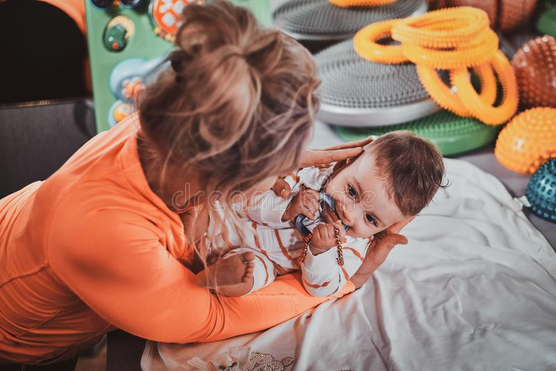 A mamã alegre plaing com seu bebê recém-nascido no armário do massagista foto de stock royalty free
