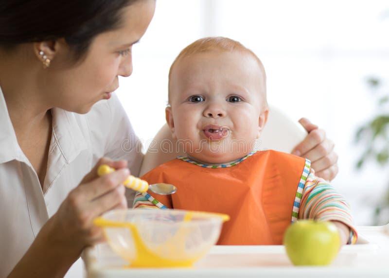 A mamã alimenta sua criança O bebê é gritando, caprichoso e de recusa comer imagens de stock royalty free