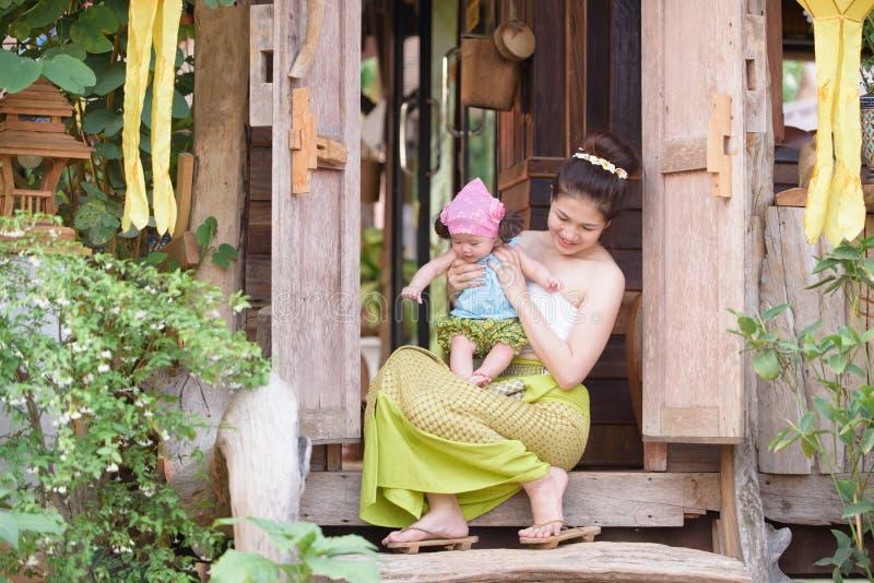 Mamã asiática feliz com a criança no terno do lanna imagem de stock royalty free