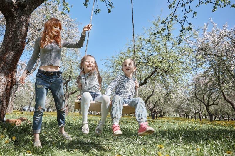 A mamã balança suas poucas filhas no balanço do jardim imagem de stock royalty free