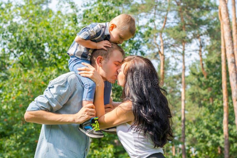 A mamã beija o paizinho que mantém sua criança foto de stock royalty free