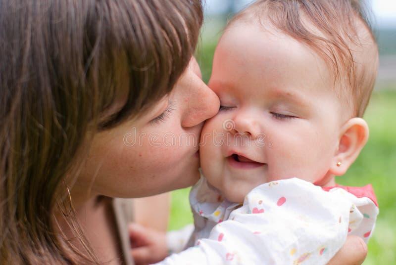 A mamã beija sua filha pequena, jogada fotografia de stock royalty free