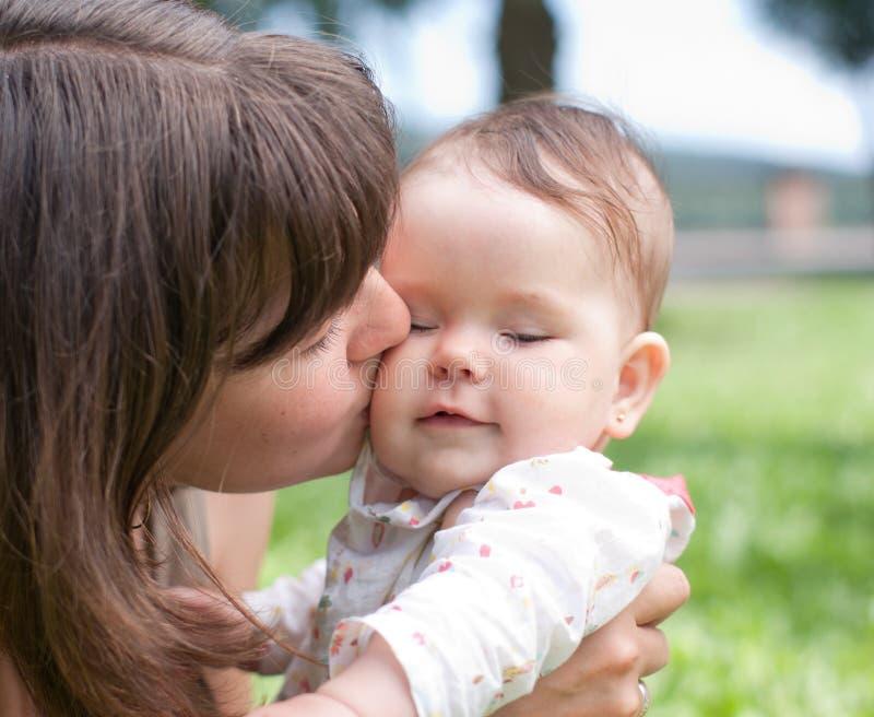 A mamã beija sua filha pequena, jogada no parque fotografia de stock