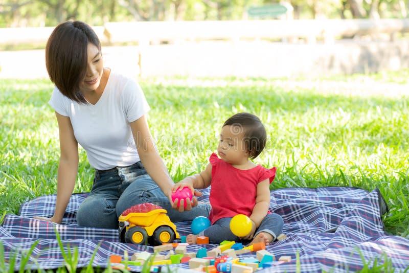 Mam? bonita e filha asi?ticas novas que jogam blocos do brinquedo para aprender o desenvolvimento feliz e o divertimento no parqu fotos de stock