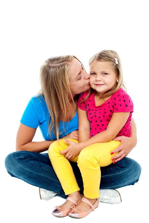 Mamã bonita que beija sua filha bonita fotografia de stock royalty free