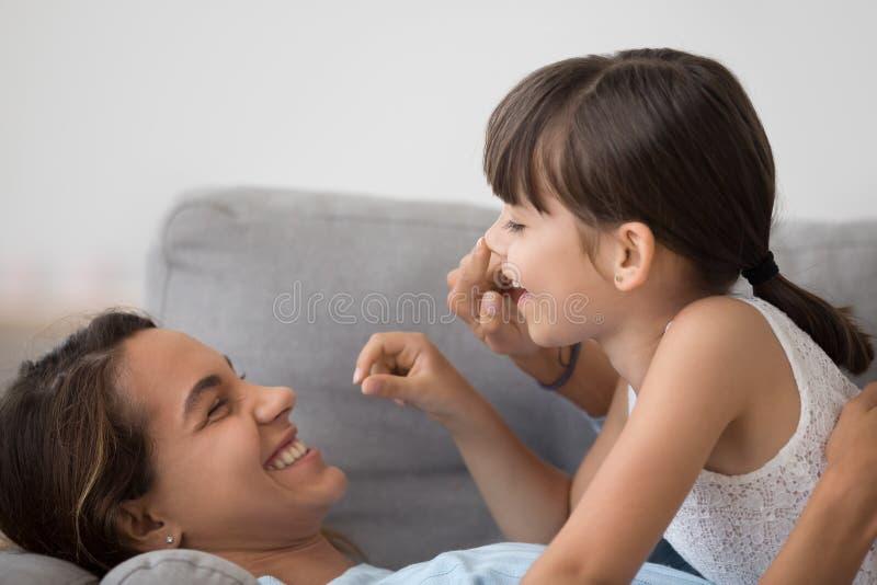 A mam? brincalh?o tem o divertimento que joga com a filha pequena bonito imagens de stock