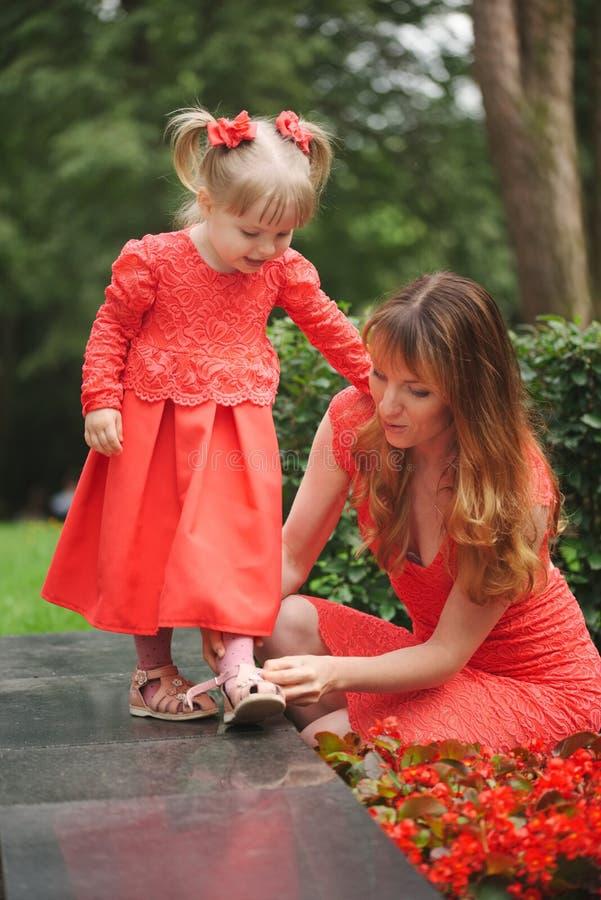 A mamã calça a filha nova no parque fotos de stock