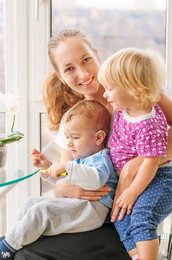 Mamã caucasiano de sorriso que guarda duas crianças fotografia de stock