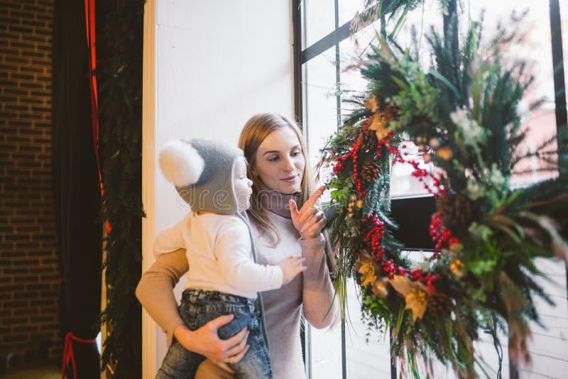 A mamã caucasiano dos feriados do ano novo e do Natal do tema guarda o filho em seus braços por 1 ano em casa em um interior do s imagens de stock