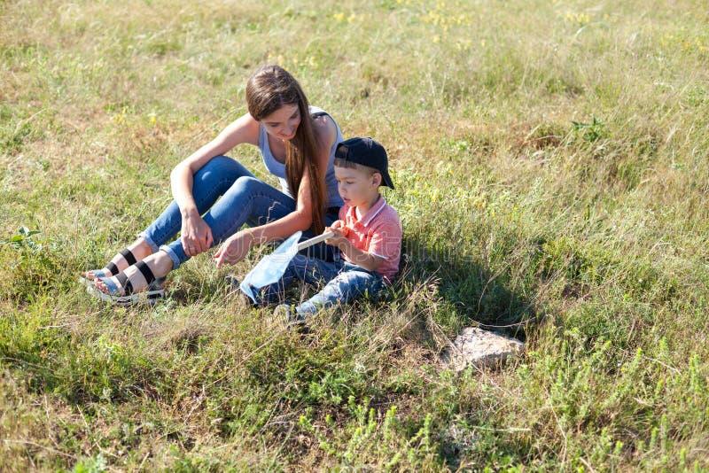 Mamã com as borboletas da captura do filho na REDE do parque fotografia de stock royalty free