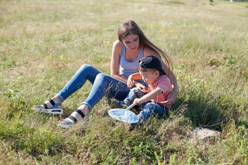 Mamã com as borboletas da captura do filho na REDE do parque foto de stock royalty free