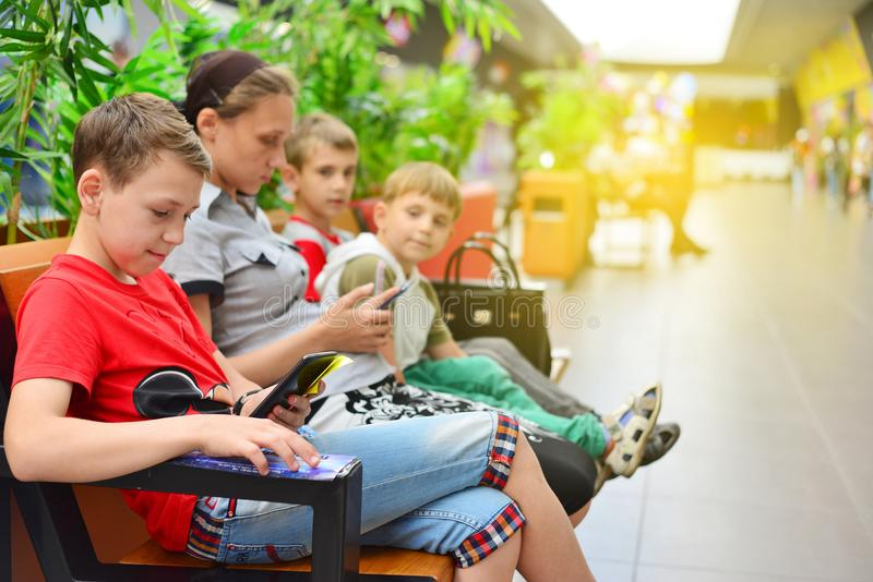 Mamã com as crianças no banco na alameda Foto com matização fotografia de stock