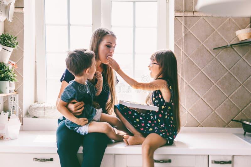 Mamã com as crianças que comem na mesa de cozinha fotos de stock royalty free