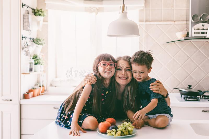 Mamã com as crianças que comem na mesa de cozinha imagens de stock