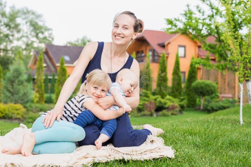 Mamã com as crianças que sentam-se em um gramado da grama verde no parque Mãe nova com a filha e o filho que têm o divertimento n imagem de stock