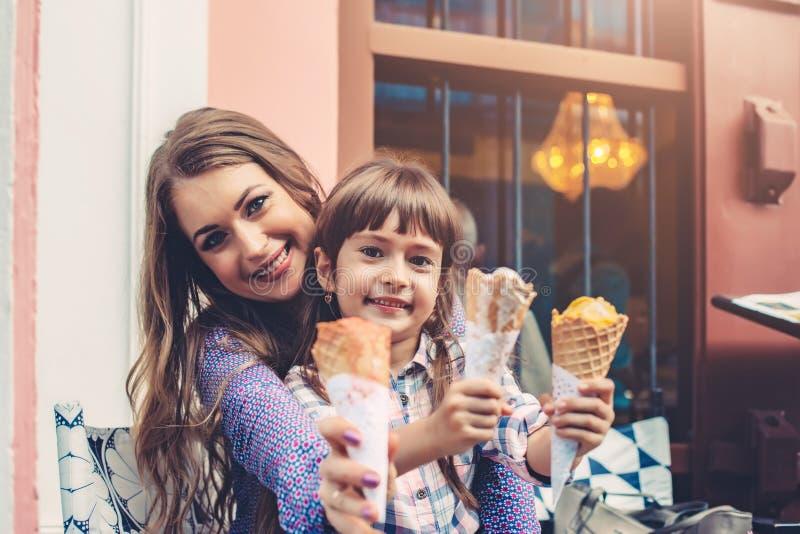 Mamã com a criança que come o gelado na rua da cidade fotografia de stock