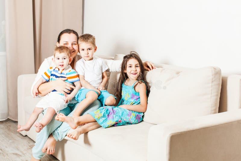 Mamã com filha e dois filhos em casa foto de stock