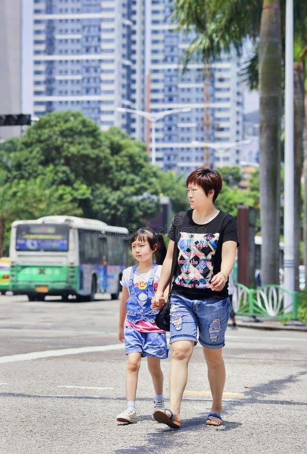 Mamã com a filha na rua, Zhuhai, China foto de stock
