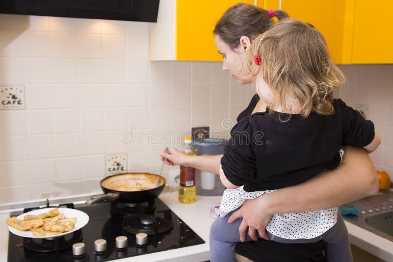 Mamã com o bebê em seus braços que preparam o alimento na cozinha Dona de casa com crianças fotografia de stock