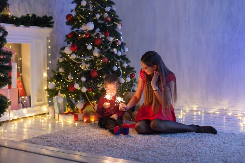 Mamã com o filho de presentes do ano novo do Natal das luzes das luzes de Bengal fotos de stock
