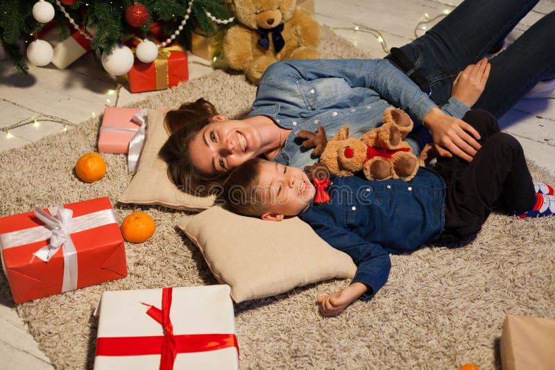 Mamã com o filho que encontra-se no assoalho perto de uma árvore de Natal com presentes fotos de stock