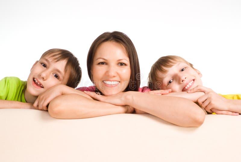 Mamã com os miúdos no sofá foto de stock