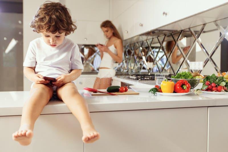Mamã com sua criança que cozinha na cozinha interior ocasional da série da foto do estilo de vida na vida real imagem de stock royalty free
