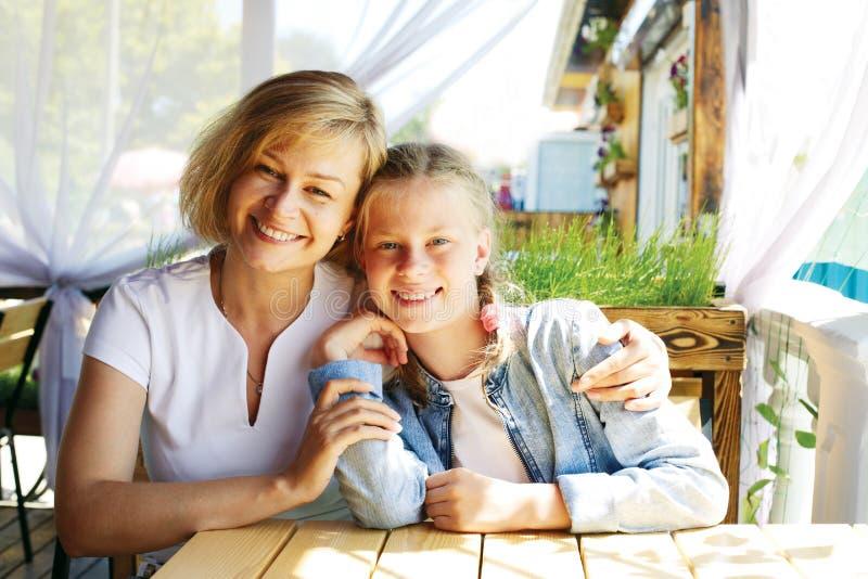 A mamã com sua filha está sentando a rua da cidade na frente do o imagem de stock