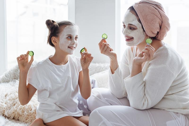 Mamã com sua filha que faz a máscara protetora da argila imagem de stock
