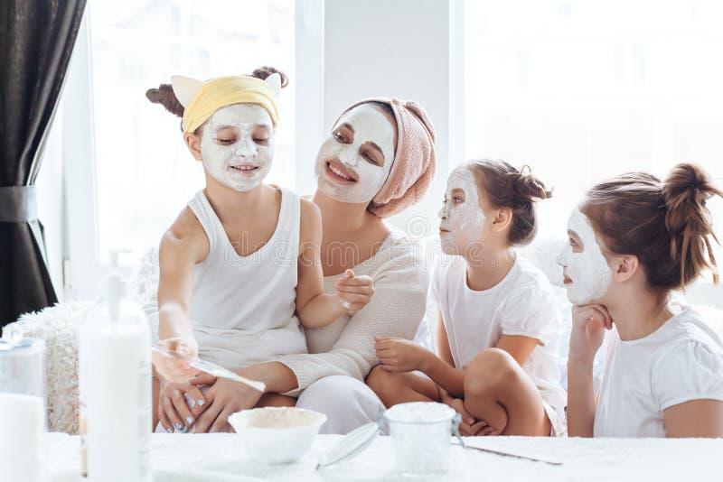 Mamã com suas filhas que fazem a máscara protetora da argila imagens de stock