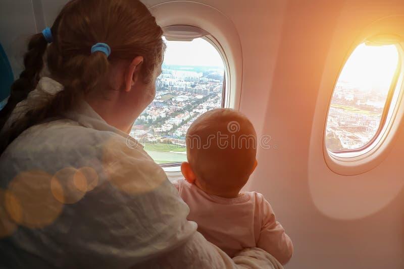 Mamã com um bebê pequeno em seu voo dos braços no plano Olham para fora a janela com interesse no interior da terra do avião foto de stock