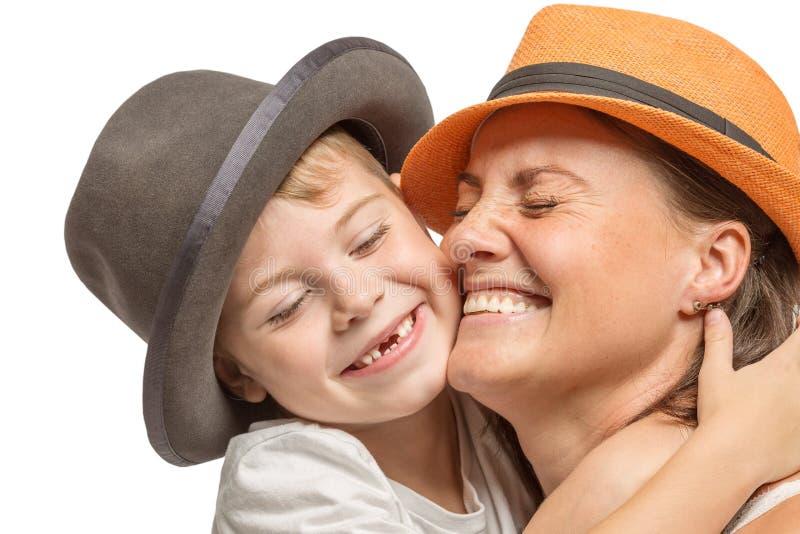 Mamã com um filho pequeno nos chapéus que abraçam e que riem, família bonito imagem de stock