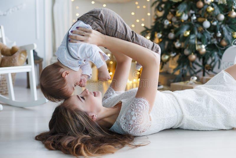 Mamã com um filho pequeno perto de uma árvore de Natal bonita em sua casa imagens de stock royalty free