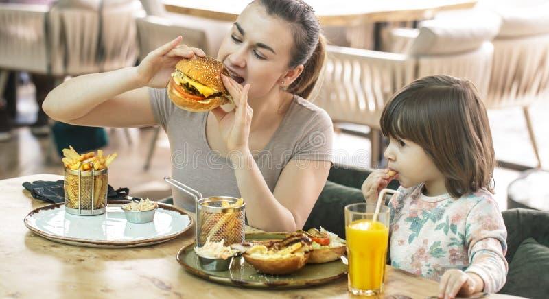 Mamã com uma filha bonito que come o fast food em um café foto de stock royalty free