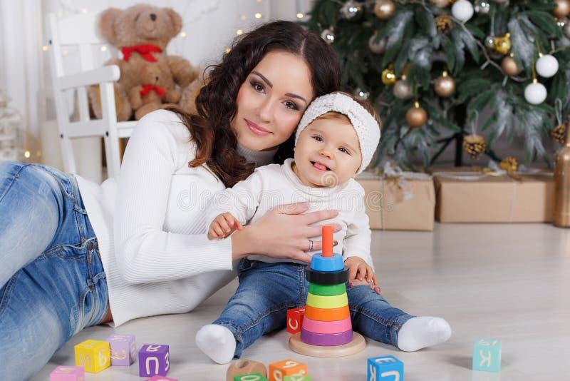 Mamã com uma filha pequena que joga na Noite de Natal no fundo de uma árvore de Natal bonita fotos de stock royalty free