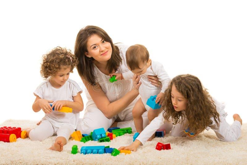 Mamã da beleza que joga com suas crianças em casa imagem de stock